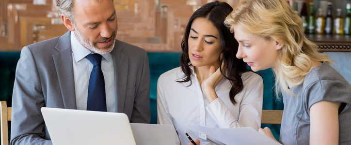 Business colleagues discussing on report with laptop on table at restaurant